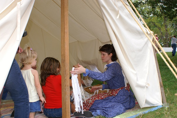 lady in period costume showing kids clothing items inside a tent