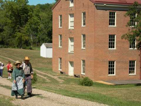 couple in period attire walking in front of the mill