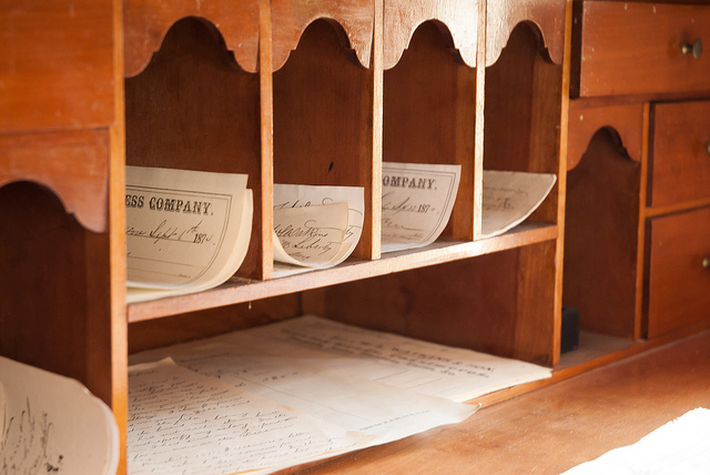 papers sorted in a wooden mail bin