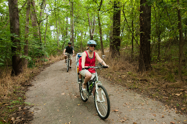 two people riding bikes on the paved trail