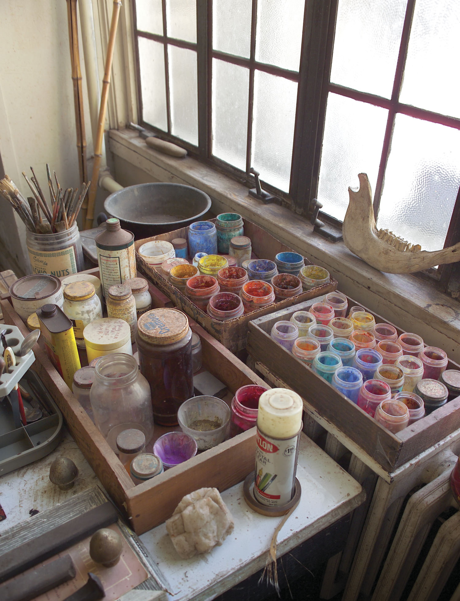 paints sit on a table next to the window in Benton's studio